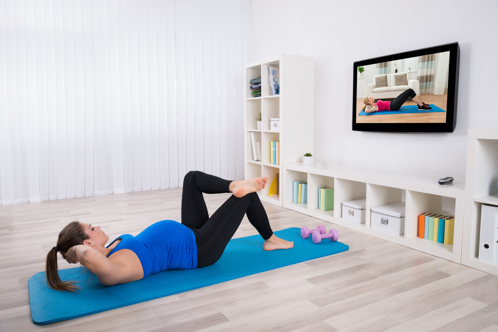 Young Pregnant Female Doing Workout In Front Of Television